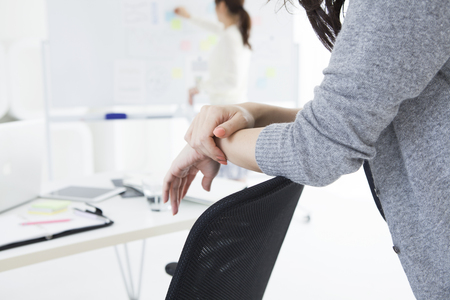 Woman standing over a hand to the office of the chair backrest