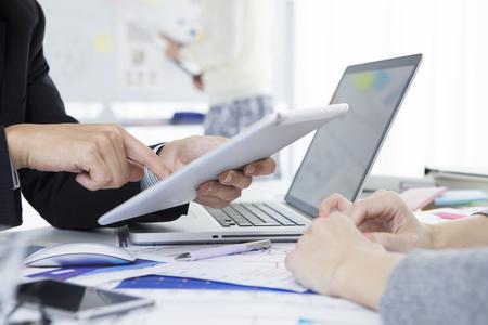 Geschäftsmann sieht in der Tablette während einer Sitzung