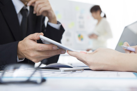Businessman is showing tablet to women during a meeting Stock Photo