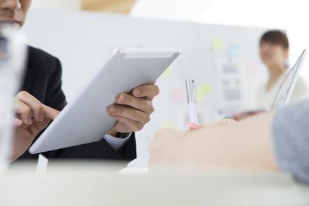 anuncio publicitario: Los hombres de negocios, están utilizando la tableta en la oficina