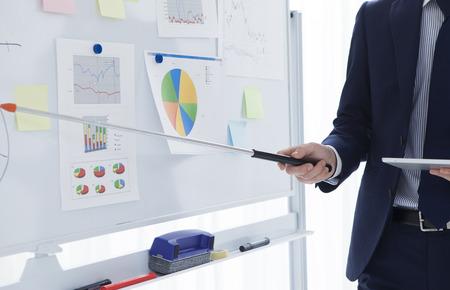 ビジネスを議論する青年実業家は、ホワイト ボードを指差しながらフレームの右側にいる視聴者に直面している予定です。 写真素材