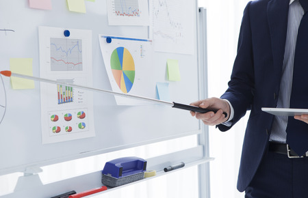 Young Businessman Discussing Business Plans While Pointing at the White Board and Facing the Listeners at Right of the Frame.
