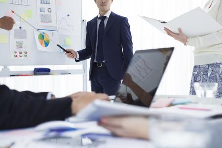 suit: Joven hombre de negocios que está en la reunión de estrategia en la oficina