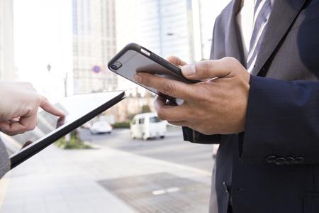 男と女のオフィス街にスマート フォンを使用するには 写真素材