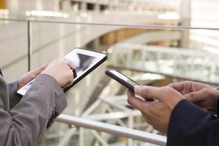 Dos personas que tocan el teléfono inteligente en el distrito de la oficina de Asia