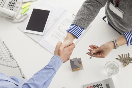 agente de bienes raíces y el cliente para darle la mano