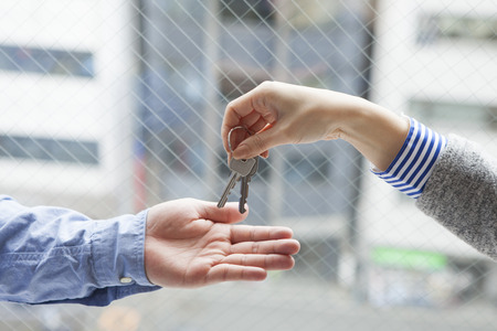 Agent nieruchomości kobieta przekazać klucz Zdjęcie Seryjne