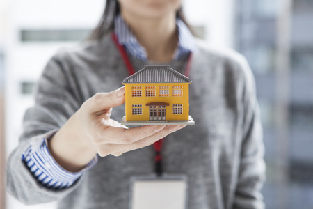 Real estate agent woman with a model of the house
