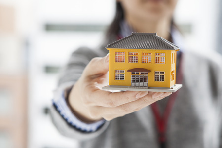 Real estate agent with a model of the house Stockfoto
