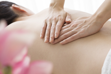 The hands of the esthetician to massage your back