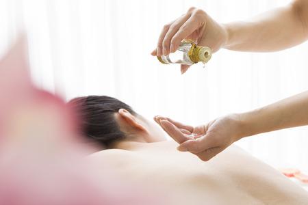massage huile: Esthéticienne à prendre l'huile à la main Banque d'images