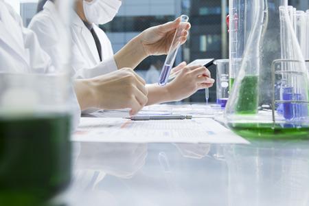 Vrouwelijke onderzoekers experimenteren met een reageerbuis