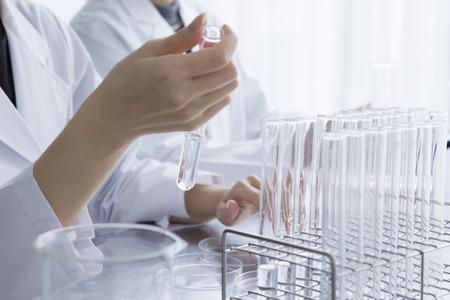 Vrouwelijke onderzoekers nemen aan de reageerbuis overhandigen