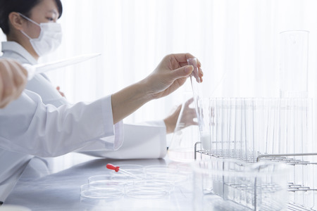 Women researchers are trying to get a test tube 写真素材