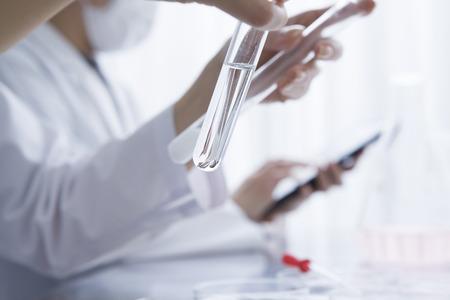 테스트 튜브의 액체에서 찾고 여성 연구원 스톡 콘텐츠