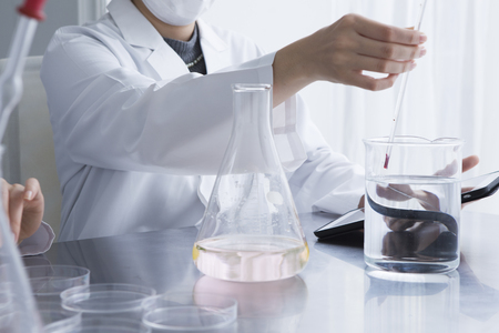 Women are measuring the temperature of the liquid in the beaker