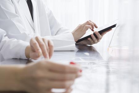 bata blanca: Los investigadores están usando tableta electrónica en el laboratorio Foto de archivo