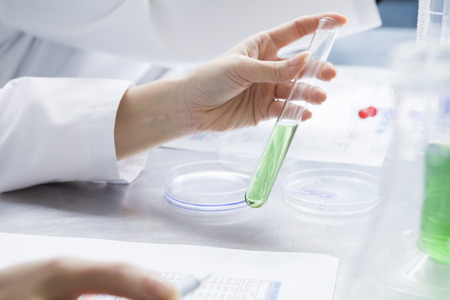 Female researcher to have a test tube of green liquid that contains Stock Photo