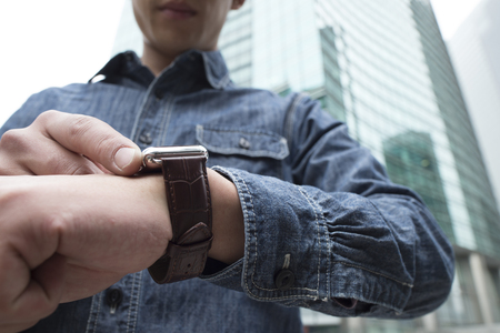 looking up: blue jacket man use the smart watch. Stock Photo