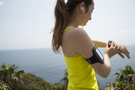 running pants: Woman wearing a yellow tank top that use the device
