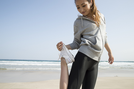 running pants: Woman to stretch on the beach