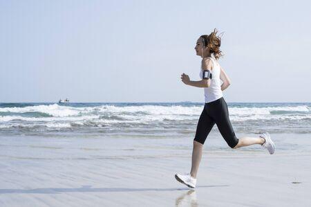 Woman wearing a white tank top that runs the seaside