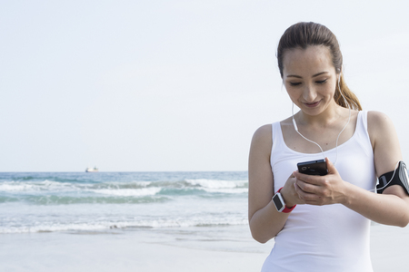 Womens white tank top to use the smart phone under the blue sky