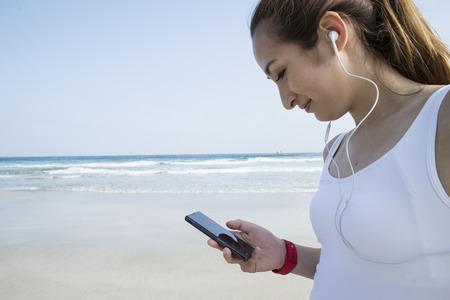 usando computadora: camiseta blanca de las mujeres a usar el teléfono inteligente bajo el cielo azul