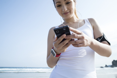 tank top: White tank top women that use the smartphone. Stock Photo