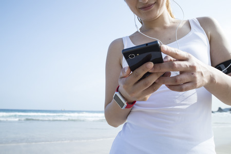 White tank top women that use the smartphone. Archivio Fotografico