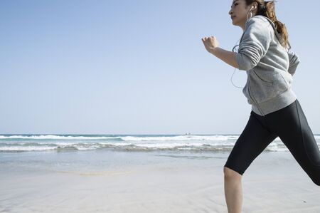 woman running: Under the blue sky, a woman running on the beach