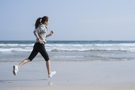 Sotto il cielo blu, una donna che correva sulla spiaggia Archivio Fotografico