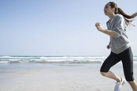 ビーチで走っている女性の青い空の下で