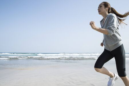 conspicuous: Under the blue sky, a woman running on the beach