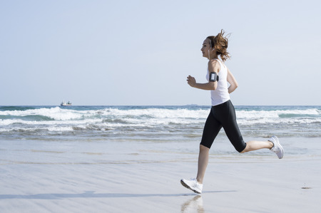 Under the blue sky, a woman running on the beach