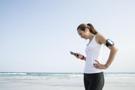 Sotto il cielo azzurro, le donne godono il telefono intelligente sulla spiaggia