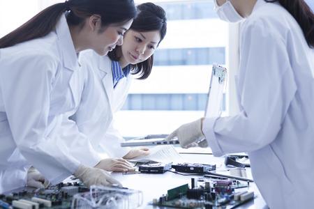3 people of genius female scientist wearing a white coat.