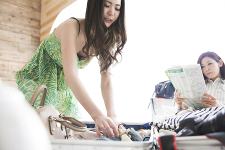 間で日当り、旅行の準備に二人の女性。スーツケース、服と夢と希望と喜びのもの。