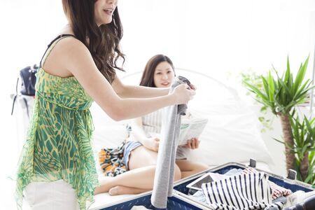 世界旅行の準備に二人の女の子。スーツケース、服と夢と希望と喜びのもの。