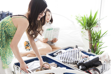 Among the nice sunshine, two women to prepare for the trip. The stuff in the suitcase, clothes and dreams and hope and joy. Stock Photo