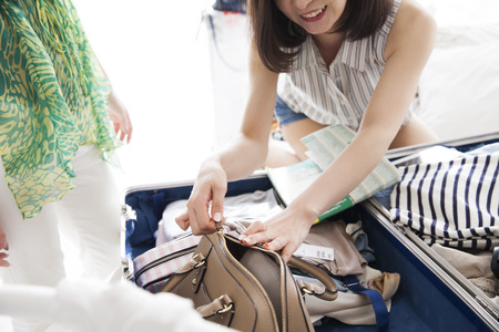 eye traveller: Among the nice sunshine, two women to prepare for the trip. The stuff in the suitcase, clothes and dreams and hope and joy. Stock Photo