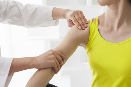 Physiotherapist stretching a woman's arm in the medical office.