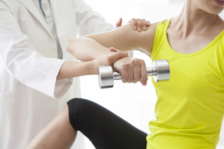 remedial: Physiotherapist stretching a womans arm in the medical office. Stock Photo