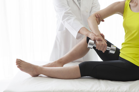 Physiotherapist stretching a womans arm in the medical office. Stock Photo