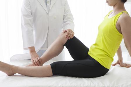 젊은 여자의 오른쪽 다리를 스트레칭하는 안마사.