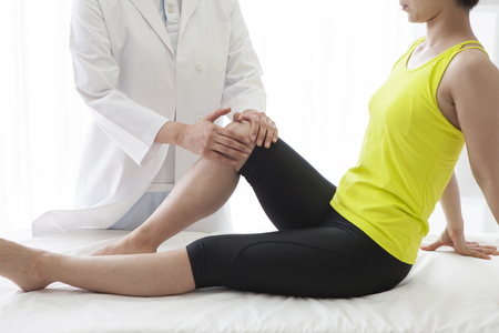 Masseuse stretching the right leg of a young woman.
