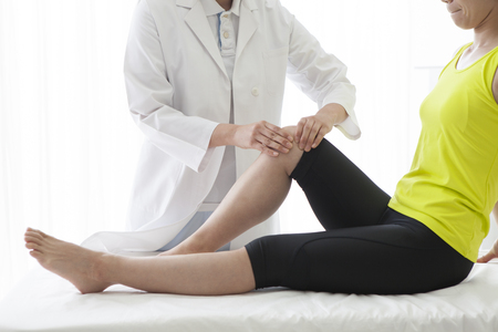 Patient at the physiotherapy doing physical therapy exercises with his therapist.