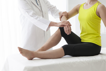 Therapist doing rehabilitation massage with hands on female...