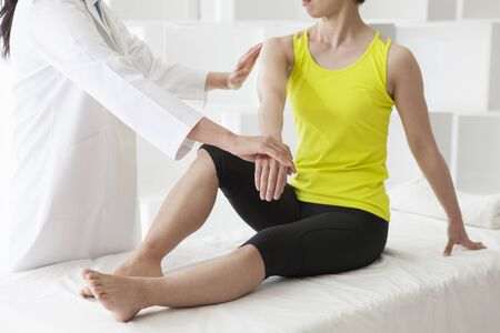 remedial: Adult female physiotherapist treating the foot of a female patient. Patient is sitting on a bed.