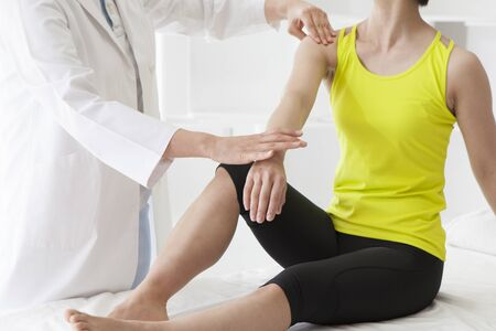 Adult female physiotherapist treating the foot of a female patient. Patient is sitting on a bed.